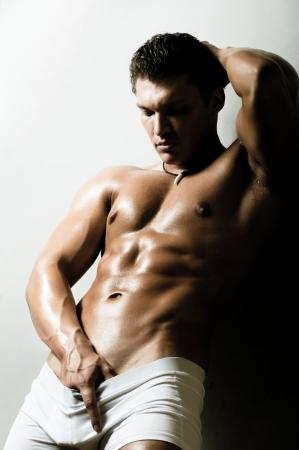 uomo nudo: il bel ragazzo molto muscoloso sexy su sfondo grigio scuro