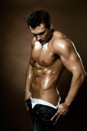 uomo nudo: il bel ragazzo molto muscoloso sexy su sfondo marrone scuro, il torso nudo Archivio Fotografico