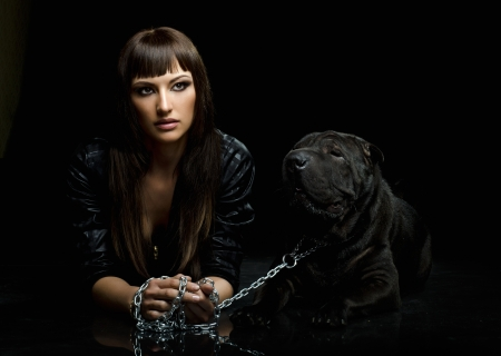 aegis: the beautiful  young woman lie with dog on black background