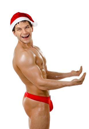 male nude: il molto muscoloso bronzato bello sexy Babbo Natale su sfondo bianco, la postura e di scoppiare a ridere, isolato