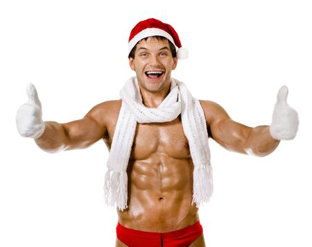 the very muscular  bronzed handsome sexy Santa Claus in red muffler on white  background, thumb up and smile, isolated Stock Photo - 15165311