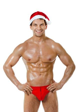 desnudo masculino: la muy musculoso bronceado guapo sexy Santa Claus sobre fondo blanco, la postura y la sonrisa, aislado
