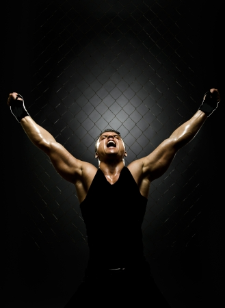 victory: vertrical photo  muscular young  guy street-fighter,  triumphant cries  yell , hard light