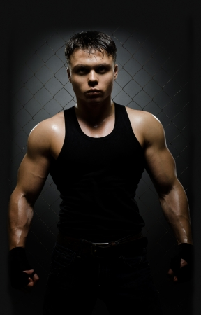 malice: vertical photo  muscular young  guy street-fighter,  aggression look, hard light