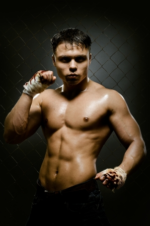 vertical photo  muscular young  guy street-fighter,  aggression look, hard light Stock Photo - 15497213