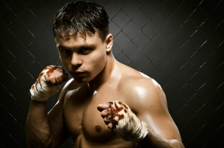 fiercely: horizontal portrait  muscular young  guy street-fighter,  aggression look, hard light