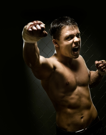 vertical photo  muscular young  guy street-fighter, cuff  fist close up on camera and yell , hard light Stock Photo - 15497193