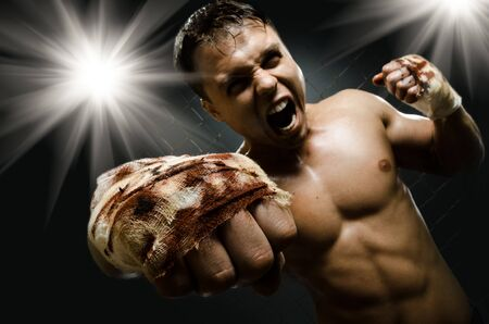 horizontal  photo  muscular young  guy street-fighter, cuff  fist close up on camera and yell , hard light Stock Photo - 15497201