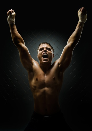 intrepid: vertrical photo  muscular young  guy street-fighter,  triumphant cries  yell , hard light