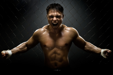 aggressive people: horizontal photo  muscular young  guy street-fighter,  aggression frightening  yell , hard light