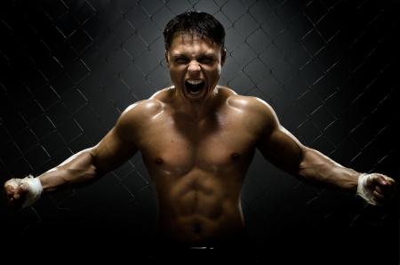 savaşçı: yatay fotoğraf kaslı genç bir adam sokak savaşçısı, saldırganlık korkutucu bağırtı, zor ışık Stok Fotoğraf