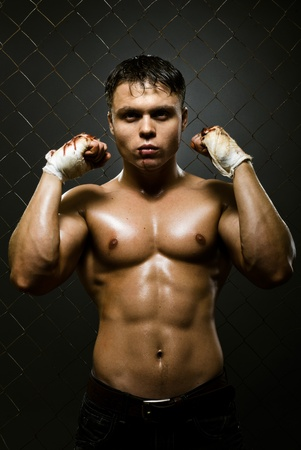 vertical photo  muscular young  guy street-fighter,  aggression look, hard light Stock Photo - 15236133