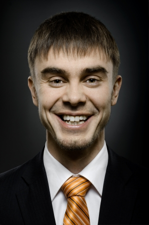 affability: close up portrait  the  beautiful  happy businessman in black costume and orange necktie, big smile Stock Photo