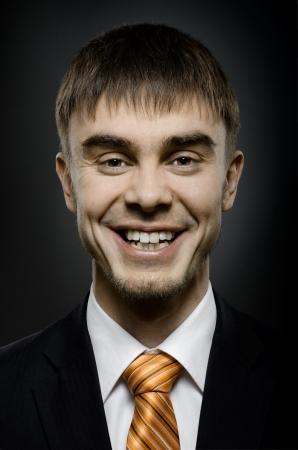 affability: close up portrait  the  beautiful  happy businessman in black costume and orange necktie, big smile Stock Photo