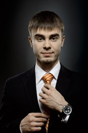 exacting: portrait  the  beautiful  businessman  in black costume tie one