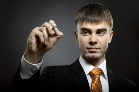 portrait  the  beautiful  businessman in  costume, hold marker in hand and write Stock Photo - 15497210