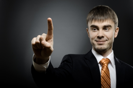 handsome businessman  finger point touch, on dark grey background Stock Photo - 15497173