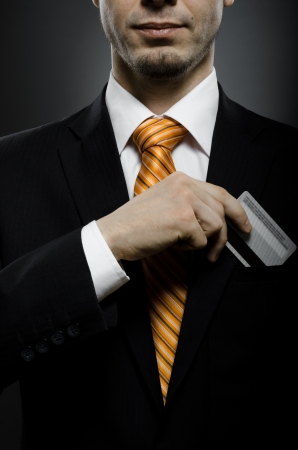 cash card: businessman in black costume and orange necktie put or take out credit card in pocket Stock Photo
