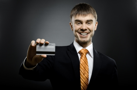 happy businessman reach out on camera and show credit card or visiting card, smile Stock Photo - 15497176