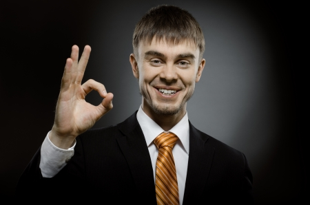 affability: horizontal portrait  the  happy beautiful  businessman in black costume , to give hand gesture o k
