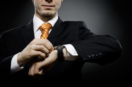 relógio: empresário em preto traje vento relógio de pulso na mão