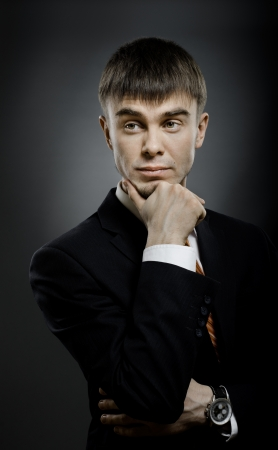 exacting: vertical portrait  the  young businessman  in costume , fixed look, on dark blue background