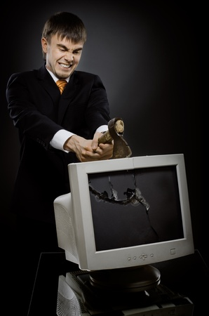 passe: frenzy businessman chop-down old monitor on dark grey background Stock Photo