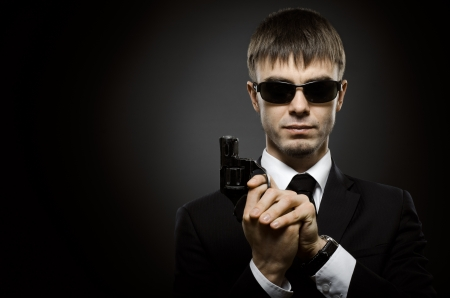 delinquent: portrait the beautiful  man in black costume,  special-service agent or  body guard with  pistol