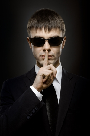 stringent: vertical portrait  the  beautiful businessman in dark-blue costume, secret concept Stock Photo