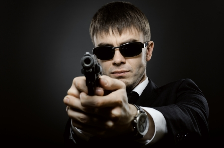 delinquent: portrait  the  beautiful  man in black costume,  special-service agent or  body guard with  pistol Stock Photo