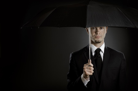 undercover agent: portrait  man the  beautiful  man in black costume with blak umbrella,  special-service agent or  body guard