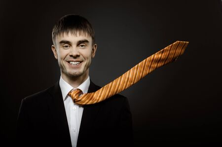 potentiality: portrait  the  happy beautiful  businessman careerist in black costume and orange necktie