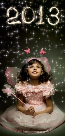 beautiful  little girl with wings, sit and  smile on dark background Stock Photo - 15224300