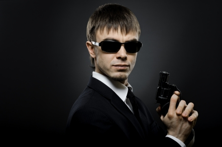 portrait the beautiful  man in black costume,  special-service agent or  body guard with  pistol photo