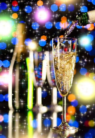 strew: bottle  champagne  stream and  splash in  glass goblet Stock Photo