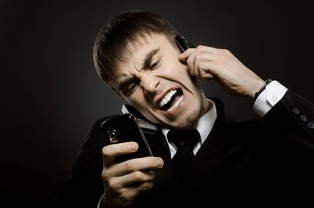 closeup portrait  the  beautiful  businessman careerist in black costume,  call and angry cry Stock Photo - 15260044