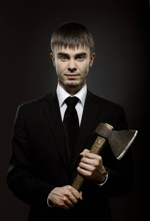 malefactor: portrait the businessman  in black costume and black necktie with axe Stock Photo