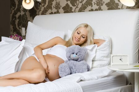 fetation: happy young pregnant woman lie in bed,  in  bedroom