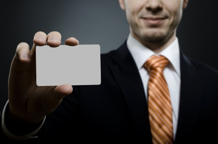 businessman in black costume and orange necktie reach out on camera and show credit card or visiting card, close up Stock Photo - 15367792