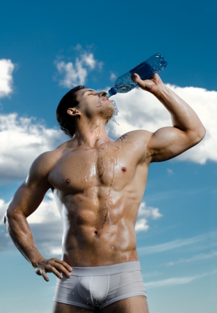 muscularity: the very muscular handsome sexy guy on sky background, drink water, focus on face