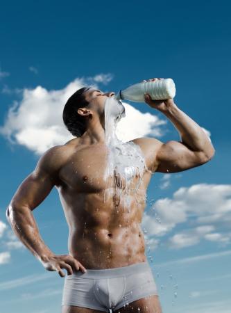 uomini nudi: il bel ragazzo molto muscoloso sexy su sfondo cielo, bere il latte, concentrarsi sul viso