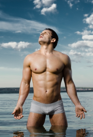 nude wet: the very muscular handsome sexy guy in water, on  sky  background Stock Photo