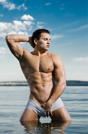 aqua naked: the very muscular handsome sexy guy in water, on  sky  background Stock Photo
