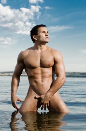 naaktstrand: de zeer gespierde knappe sexy man in het water, op hemelachtergrond