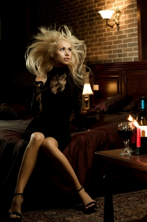 the very  pretty woman indoor in interior  bedroom, blonde  tousled long hair