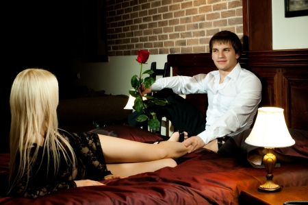 lovers in bed: romantic evening date in hotel room, guy with  sexy girl on bed Stock Photo