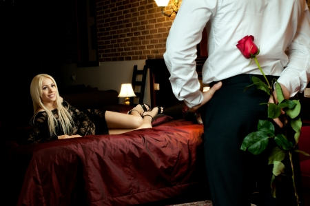 romantic sexy couple: romantic evening date in hotel room, guy with  sexy girl on bed Stock Photo