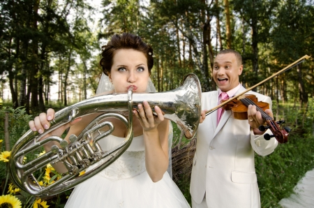 fiancee blow the trumpet,  bridegroom play on violin, wedding  humour photo