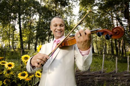guy bridegroom play on  violin and smile, in wedded day photo
