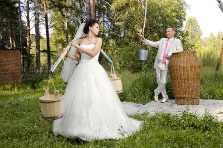 fiancee:  beautiful fiancee with yoke and  bucket, wedding humour photo